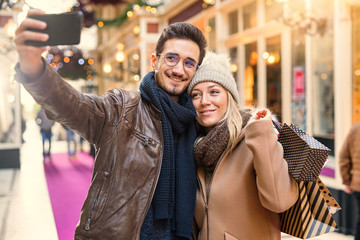 A young couple do a selfie in the decorated street for Christmas