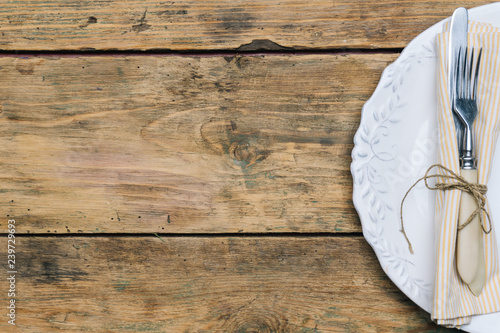 Empty white rustic plate on old wooden background with knife