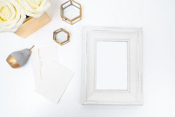 White frame flat lay with glass box and gold vase
