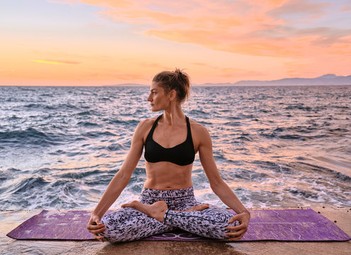 Woman meditating near sea
