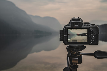 camera on tripod at work on a misty lakeshore