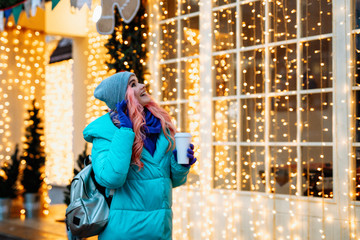 Cute young girl with pink hair walks down the street in winter and admires the lights of the city