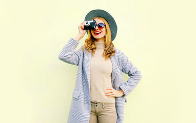 Stylish pretty smiling woman holds retro camera taking picture on background