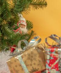 Дед Мороз смотрит из-за елки на подарки