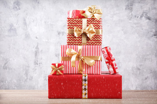 Christmas preparation concept. Stack of different colorful presents for every family member. Pile of gifts in bright festive wrapping. Close up, copy space grunged concrete wall background.