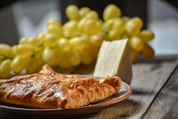 Traditional bread pita or khachapuri on the table with herbs. Homemade baking recipe.