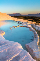 Pools of Pamukkale in Turkey in sunset, contains hot springs and travertines, terraces of carbonate minerals left by the flowing water, UNESCO World Heritage Site