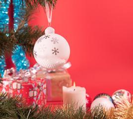 Белый елочный шар со снежинками висит на елке с подарками и горящей свечой