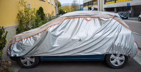 Auto durch eine Schutzhülle vor schlechter Witterung geschützt