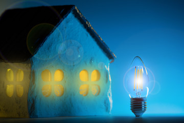 Silhouette led lamp against layout of the house on a blue background
