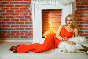 beautiful young woman in red dress lying by the fireplace.