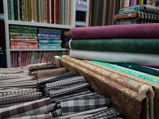 Rolls of fabric and checkered textiles and other designs and colors in a factory shop, store or bazaar