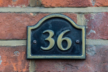 The house number 36 in brass on a red brick wall,