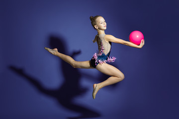 girl gymnast performs a jump with the ball. Frozen motion. Violet background. A child in a bathing suit for rhythmic gymnastics.