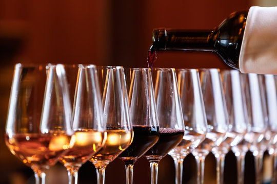 Wine glasses in a row. Pouring wine. Buffet table celebration of wine tasting. Nightlife, celebration and entertainment concept
