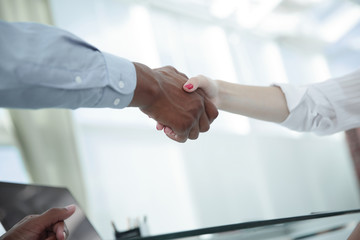 closeup.strong financial partners shaking hands over a Desk