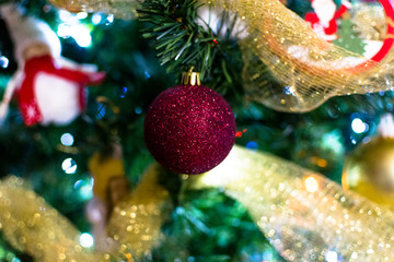 golden details in christmas tree with balls and bokeh blurred leds