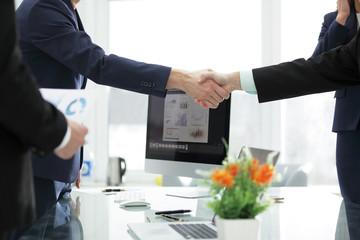 close up.handshake of financial partners on desktop background