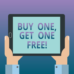 Handwriting text writing Buy One Get One Free. Concept meaning Promotion discount special offering in gift card Hu analysis Hand Holding Blank Screen Tablet Smartphone Display Unit photo