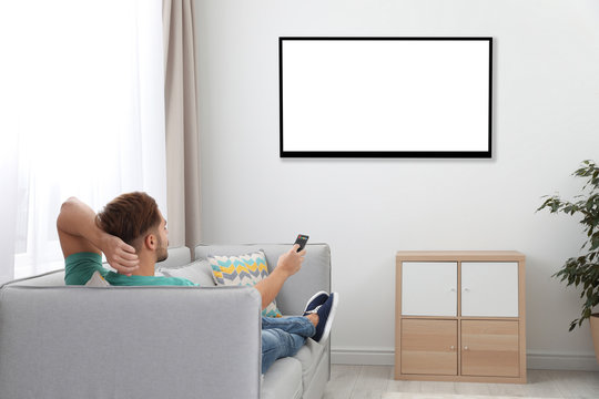 Young man watching TV on sofa at home. Mockup for design