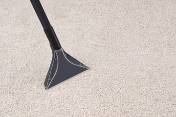 Removing dirt from carpet with vacuum cleaner indoors, closeup. Space for text