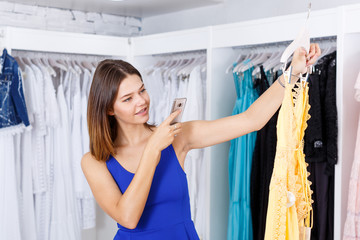 Woman choosing dress and taking photo on her phone