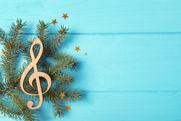 Composition with decorative treble clef and space for text on wooden background, top view. Christmas music concept
