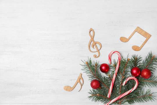 Composition with decorative music notes and space for text on wooden background, top view