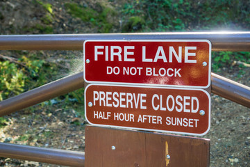 """""""Fire Lane; Do not block"""" and """"Preserve Closed Half Hour After Sunset"""" signs posted in one of the parks of San Francisco bay area, California"""