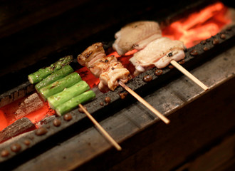 """Yakitori grilled chicken on skewers are cooked by Hiroyuki Seo, chef and owner of the Japanese restaurant """"Torizen Seo"""", at his restaurant in Tokyo"""