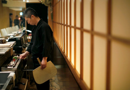 """Hiroyuki Seo, chef and owner of Japanese restaurant """"Torizen Seo"""" cooks yakitori grilled chicken on skewers in Tokyo"""