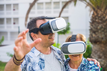 technology concept for no young people middle age and mature man and woman enjoying the outdoor leisure activity with virtual realituy 3d playful lifestyle together laughing and smiling