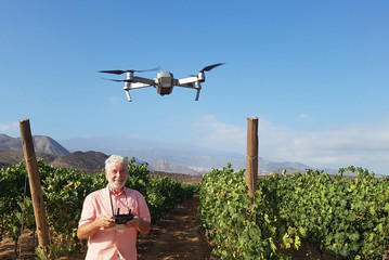 Happy caucasian adult senior man use a technology modern drone and enjoy taking pictures and video from above the ground - hobby for retired people - top view