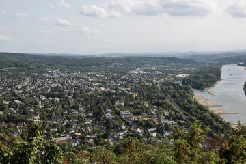Bird's eye view of a city from Drachenfels Hills. The city looks congested with lush greeneries and mountains. A river can be seen flowing with boats floating on it.