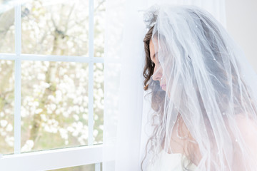 Closeup side, profile portrait of young female person, woman, bride in wedding dress, veil, face, pearl necklace, hair, standing, looking down, view through glass window, sad, white curtains, thinking