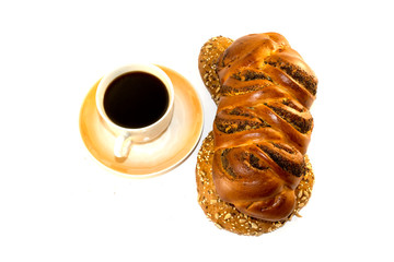 Cup of black coffee and braided bread with poppy seeds on white isolated background.