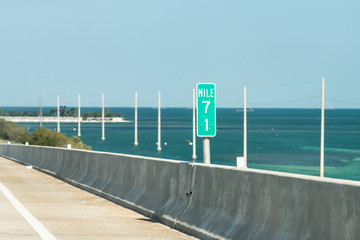 Bahia Honda Key, USA Mile 71 marker, mark, green sign at overseas highway road, blocks, ocean, sea on bridge passage in Florida