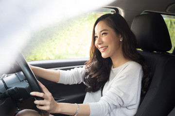 Asian women driving a car and smile happily with glad positive expression during the drive to travel journey, People enjoy laughing transport and relaxed happy woman on roadtrip vacation concept Wall mural