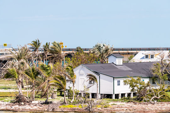 Many damaged, destroyed elevated, raised piling stilt houses on beach by shore, coast in Florida keys, bridge after, aftermath of destruction of hurricane irma, houses after storm heavy wind