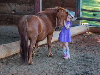 Small cowgirl in a blue dress and hat, hugging her shetland pony in the stable yard.