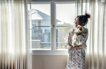 Young woman is carrying a white puppy cute After waking up in the morning,