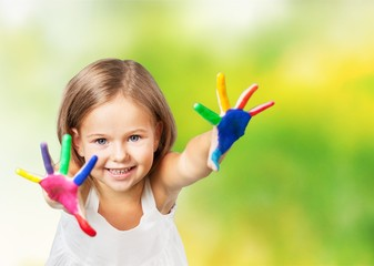 Little girl showing painted hands on bright background