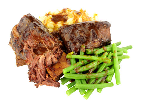 Beef short rib meal with creamy mashed potato and gravy isolated on a white background