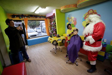 The owner of a kids hair salon, dressed as Santa Claus, poses for a photo next to a hairstylist cutting the hair of a child, in Monterrey
