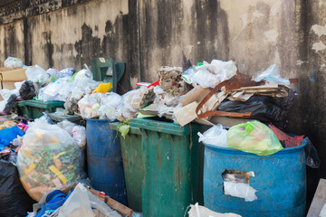 Stack of different types of large garbage dump, plastic bags, and trash bins near a wall in urban area in Environmental pollution concept in Bangkok city, Thailand