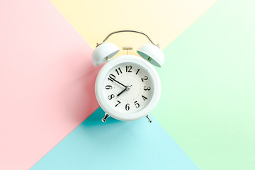 White alarm clock on colorful background. Trendy minimal style. Beauty and fashion concept. Flat lay composition. Top view.