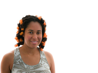 A head shot of a young beautiful adult female mixed African American woman wearing a gray tank top pajama top and orange beauty curlers or rollers in her dark hair isolated on a white background.