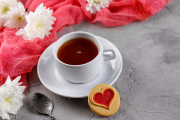 Cup of tea and cookies with hearts on a gray background. Beautiful still life with a cup of tea, the mood of Valentine's Day.