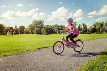 Girl in a helmet riding a bicycle. Cyclist in summer park. Wall mural