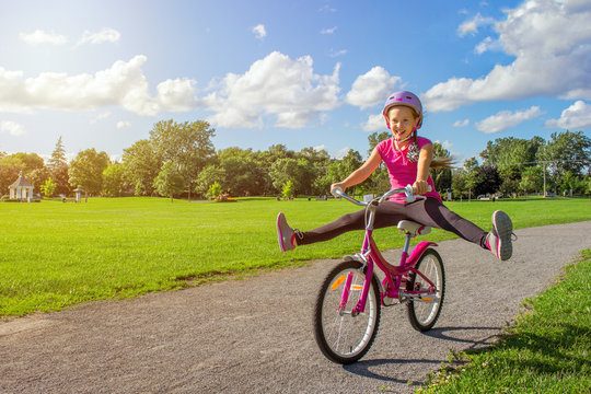Girl in a helmet riding a bicycle. Cyclist in summer park.